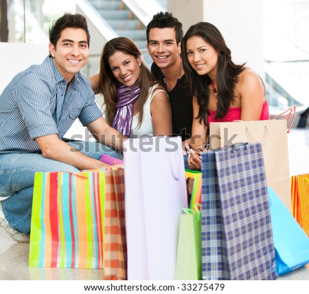 Group of friends with bags at a shopping center - stock photo