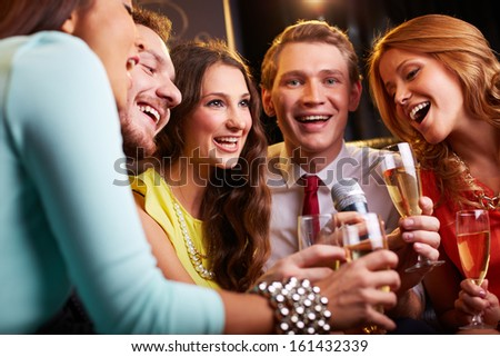 Group of friends with flutes of champagne singing in the bar