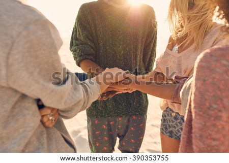 Group of friends with hands on stack at seaside. Multiracial group standing together on the beach showing unity. - stock photo