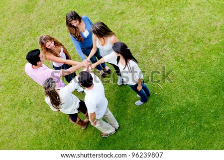 Group of friends with hands together in the middle - teamwork concepts