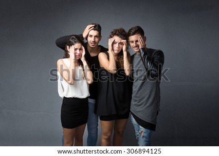 group of friends with headache , dark background - stock photo
