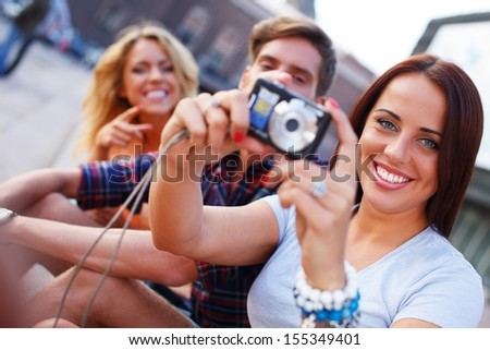Group of friends with photo camera outdoors - stock photo