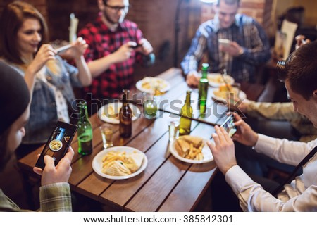 Group of friends with smartphones taking picture of food at bar or pub. Selective focus, depth of field - stock photo
