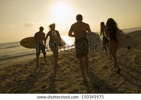 Group of friends with surfboards running towards ocean at sunset - stock photo