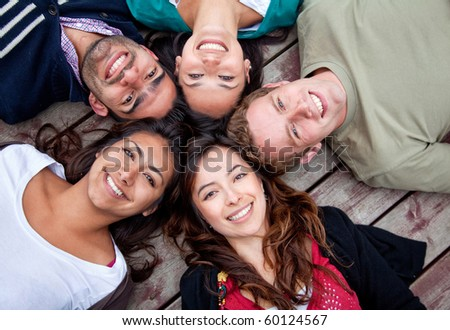Group of friends with their heads together in a circle outdoors - stock photo