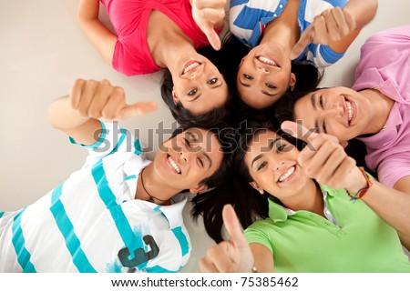 Group of friends with their heads together on the floor and thumbs up ? isolated