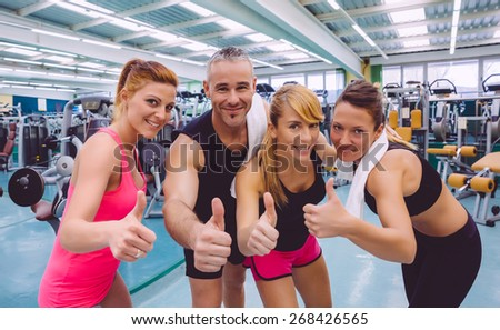 Group of friends with thumbs up smiling on a fitness center after hard training day - stock photo
