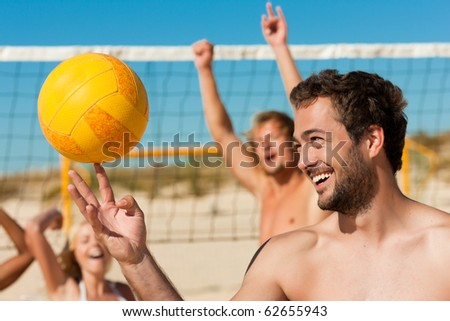 Group of friends - women and men - playing beach volleyball, one in front doing tricks to the ball - stock photo