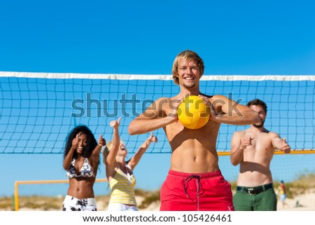 Group of friends - women and men - playing beach volleyball, one in front having the ball - stock photo