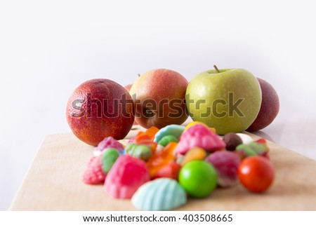 Group of fruit candy and marmalade, three red apples and red oranges