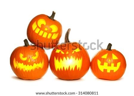 Group of fun lit Halloween Jack o Lanterns isolated on a white background - stock photo
