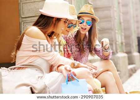 Group of girl friends resting after shopping in the city - stock photo