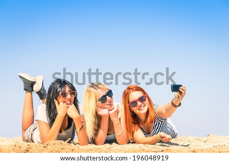Group of girlfriends taking a selfie at the beach - Concept of friendship and fun in the summer with new trends and technology - Best friends enjoying the moment with modern smartphone - stock photo