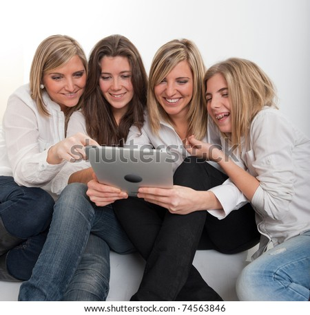 Group of girls around a pc tablet.  Please note that the logo and writing on the tablet are mine. I am attaching a property release, so no copyright issue. - stock photo