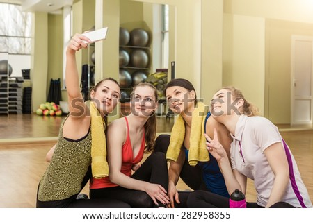Group of girls in fitness class at the break looking at smartphone - stock photo