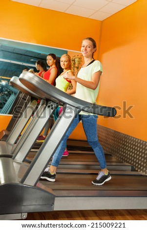 Group of girls running on the treadmill in gym  - stock photo