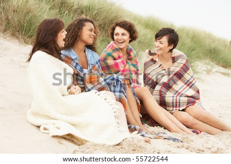 Group Of Girls Sitting On Beach Together - stock photo