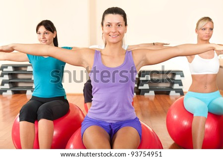 Group of girls sitting on the balls and doing back exercising - stock photo