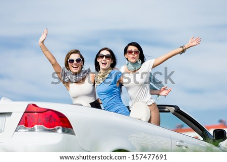 Group of girls stands in the car with hands up. Happy journey of joyful teenagers - stock photo