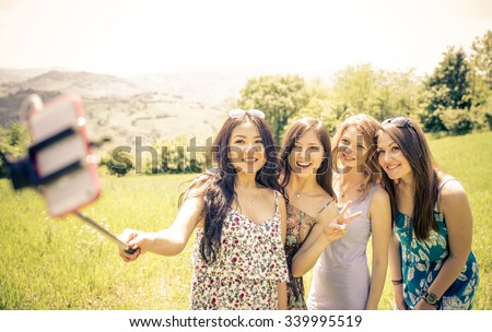 Group of girls taking selfie in the nature. concept about technology, nature and people - stock photo