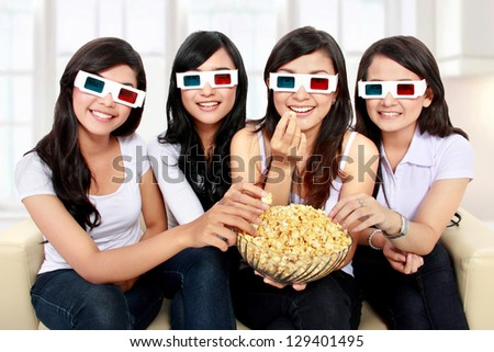 Group of girls watching movie wear 3D glasses while eating popcorn