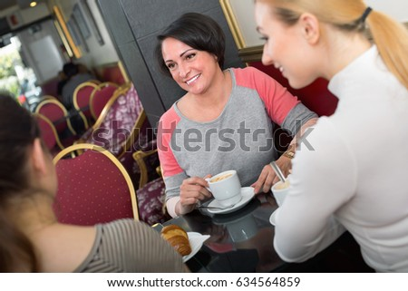 Group of glad positive smiling women taking a pleasant conversation over a cup of coffee