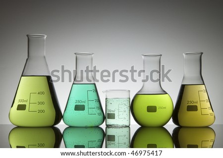 group of glasses and bottles with greenish liquid laboratory