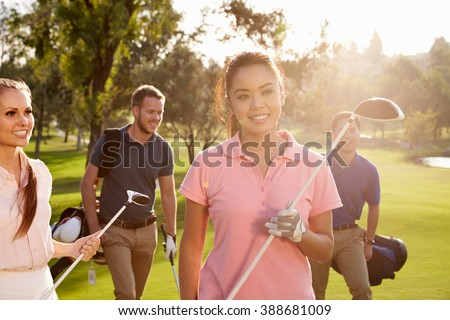 Group Of Golfers Walking Along Fairway Carrying Golf Bags - stock photo