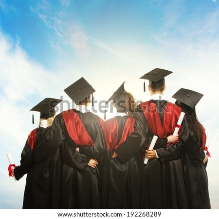 Group of graduated young students in black mantles against blue sky  - stock photo