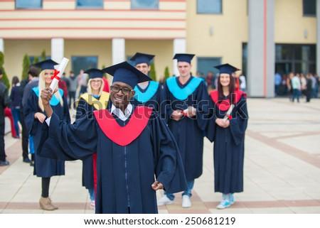 group of graduates celebrating outdoors - stock photo