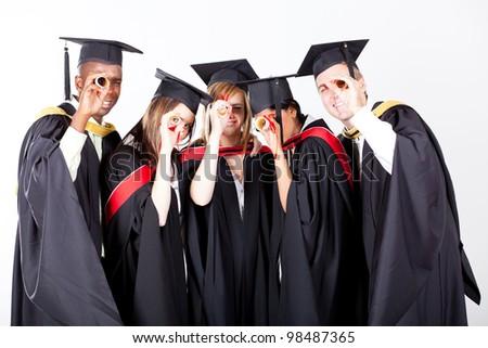 group of graduates looking through their diploma - stock photo