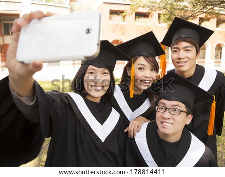 group of graduates  taking picture with cell phone - stock photo