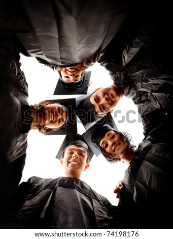 Group of graduates wearing a gown and mortarboard - isolated over white - stock photo