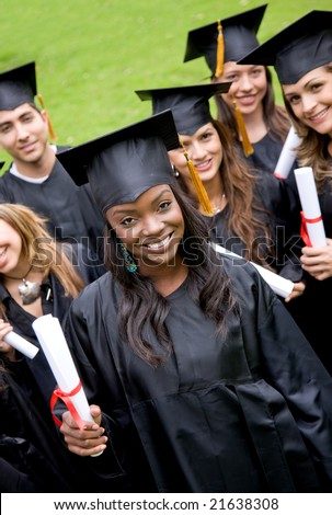 group of graduation students smiling and looking happy in their gowns - stock photo