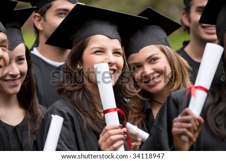 Group of graduation students with diplomas outdoors - stock photo