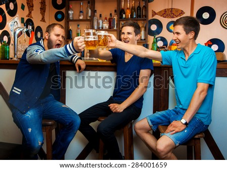 Group of guys drinking beer in a bar and have some fun. horizontal photo - stock photo
