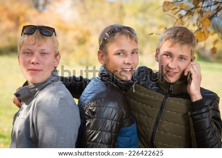Group of guys talking in the autumn park, two of the boys twin brothers. - stock photo