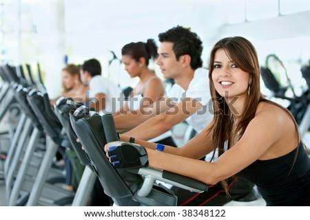 Group of gym people exercising on cardio machines - stock photo