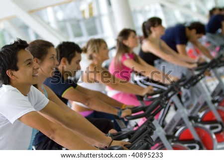 Group of gym people exercising on machines - stock photo