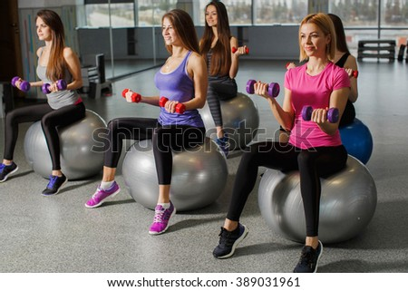 Group of Gym people exercising with Pilates fit balls. fitness, sport, training and gesture concept - group of smiling women showing thumbs up in gym. Group of people in a pilates class at gym - stock photo