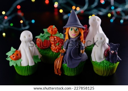 Group of Halloween cupcakes decorated with sugar figures witch ghosts and pumpkin upper-angle view. - stock photo