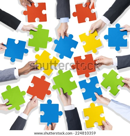 Group of Hands Holding Colorful Jigsaw Pieces - stock photo