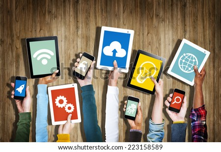 Group of Hands Holding Digital Devices with Symbols - stock photo