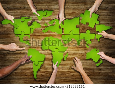 Group of Hands Holding Jigasw Puzzle Forming World - stock photo