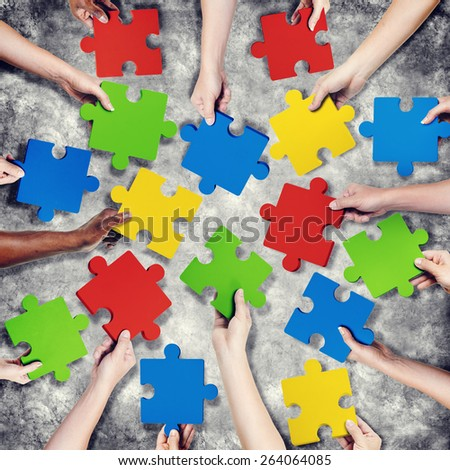 Group of Hands Holding Jigsaw Puzzle - stock photo