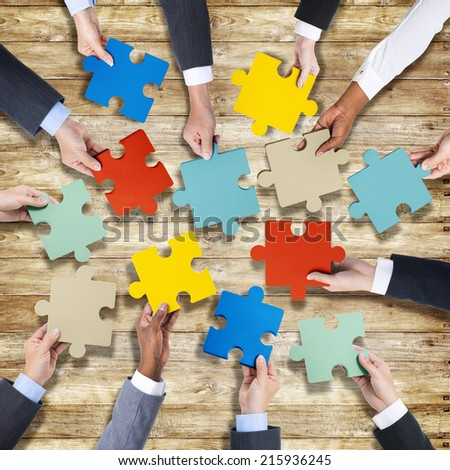 Group of Hands Holding Jigssaw Puzzle - stock photo
