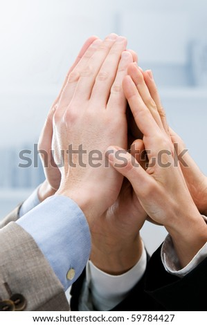Group of hands raised up for an high five in the office. Symbol of teamwork, victory and success - stock photo