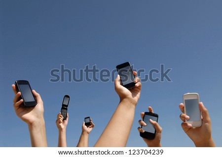 Group of hands with different cellphones connecting - stock photo