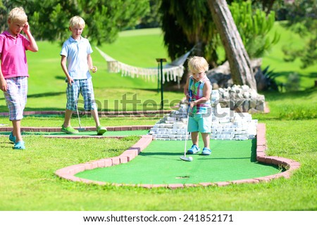 Group of happy active children, two brothers, teenage boys, and their little sister, cute toddler girl, playing miniature golf enjoying sunny summer vacation day outdoors in the park - stock photo