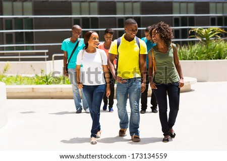 group of happy african american college students walking on modern campus - stock photo